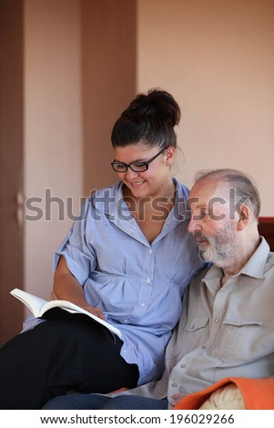young person reading book to elderly man - stock photo