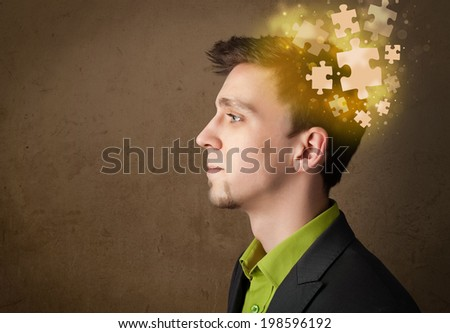 Young person thinking with glowing puzzle mind on grungy background - stock photo