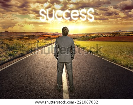 Young perspective businessman standing on asphalt highway  looking at horizon. Concept of successful future in career.   - stock photo