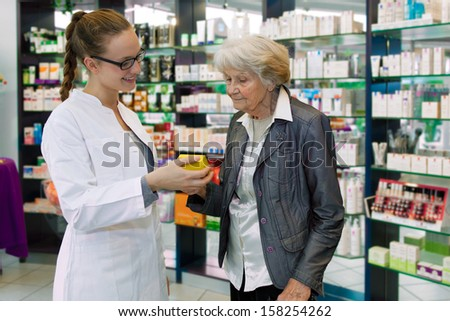 Young pharmacist giving advices about medication to senior female patient in a pharmacy - stock photo