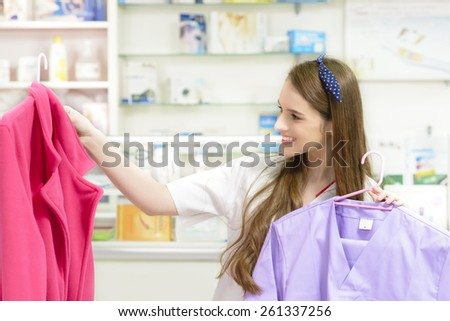 Young Pharmacist holding a medical uniform in a drugstore - stock photo