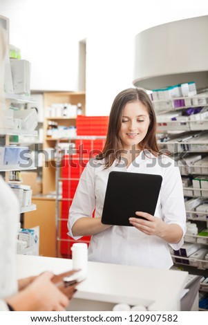 Young pharmacist with digital tablet computer helping customer - stock photo
