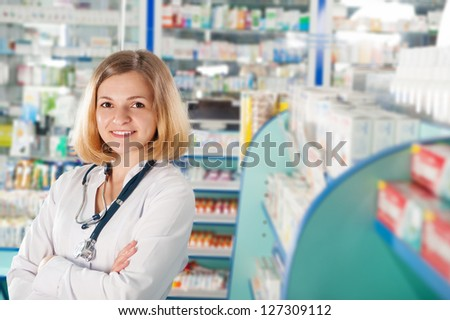 Young pharmacist with phonendoscope in drugstore - stock photo