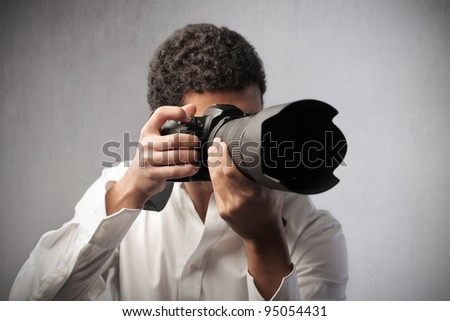 Young photograph taking pictures with a reflex camera - stock photo