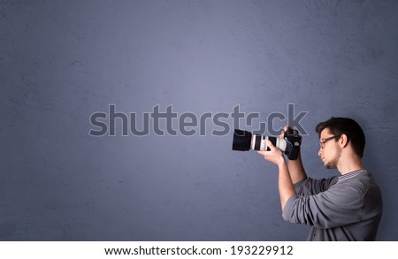 Young photographer boy shooting images with copyspace area - stock photo