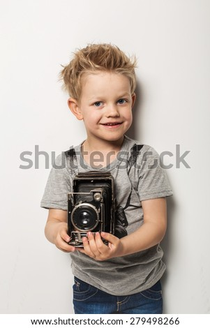 Young photographer. Little boy hold vintage camera. Studio portrait over white background - stock photo