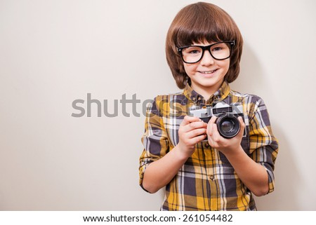 Young photographer. Little boy in eyewear holding camera and smiling while standing against grey background - stock photo
