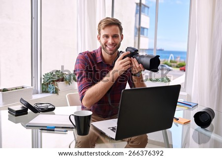 Young photographer smiling at the camera with a camera in hands, sitting at his desk where he works from home. - stock photo
