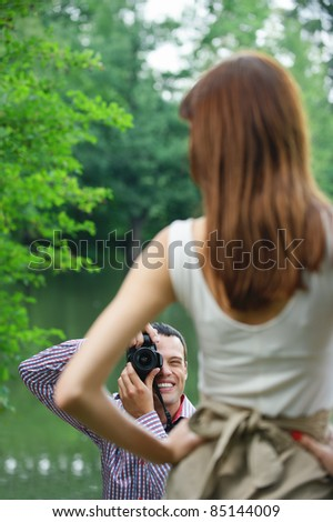 Young photographer takes photo of woman at summer green park. - stock photo