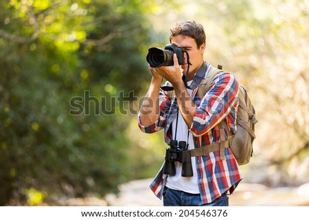 young photographer taking photos in mountain valley - stock photo