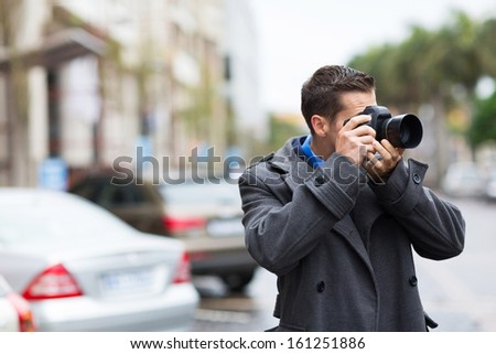 young photographer taking photos on city street in the rain - stock photo