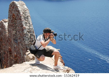 young photographer taking picture on rooftop in Santorini