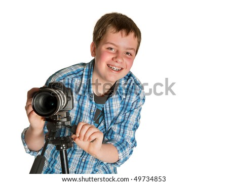 Young photographer teenager taking photos with a camera on a tripod - stock photo