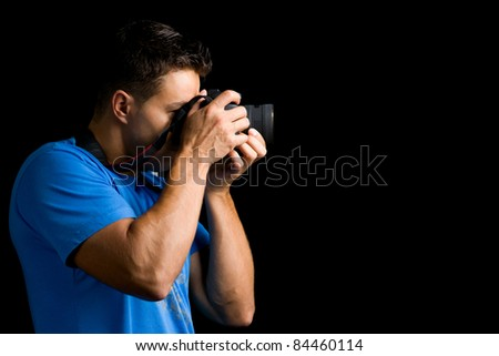 Young photographer with camera against black background - stock photo