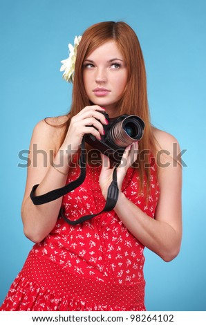 Young photographer woman holding camera against blue background - stock photo