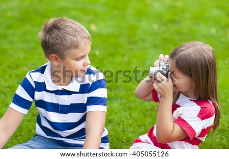 Young photographers. Pretty little brother and sister playing with a camera in summer park - stock photo