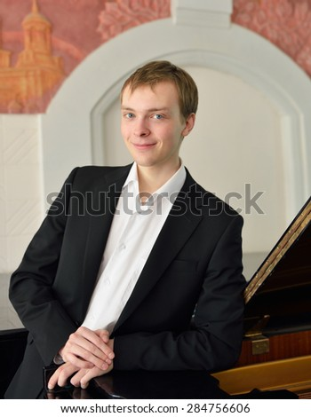 Young pianist next to black grand piano - stock photo