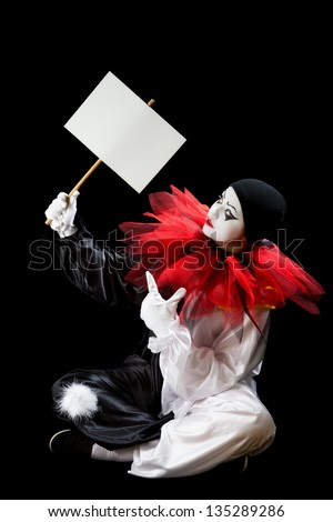 Young Pierrot sitting on a black background holding an empty sign - stock photo