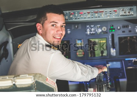 Young Pilot in the Airplane Cockpit - stock photo
