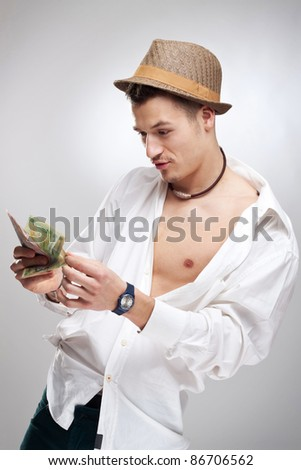 young player counting his winnings in front of a studio background - stock photo