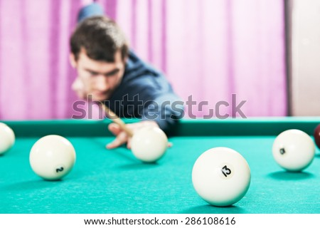Young player man with cue playing billiard or snooker game - stock photo