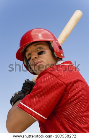 Young player ready to hit a shot against clear sky - stock photo