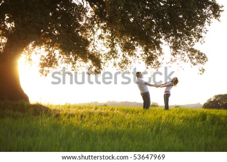 Young playful couple under huge tree at sunset - stock photo