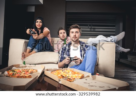 young  playing video games while sitting on sofa - stock photo
