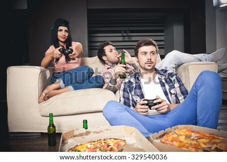 young  playing video games while sitting on sofa