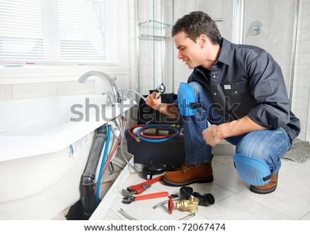 Young plumber fixing a sink. Worker at kitchen