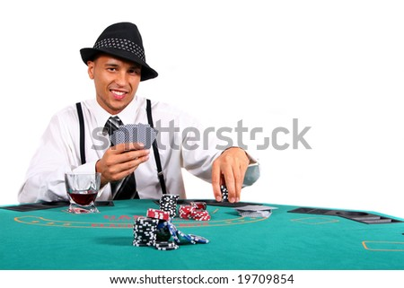 Young Poker Player On Table Young man playing poker with a hat and stylish suit. Isolated over white background. - stock photo