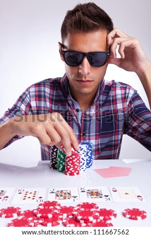 young poker player with sunglasses preparing to raise the bet - stock photo