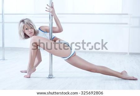 Young pole dance woman in bright white interior. - stock photo