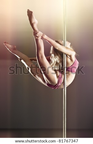 Young pole dance woman. On wall background. - stock photo