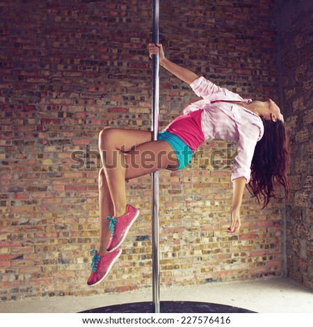 Young pole dancer woman wearing colorful sports wear and sneakers trains on grunge interior with brick walls, square composition - stock photo