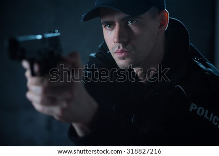 Young policeman with pistol aiming at offender - stock photo