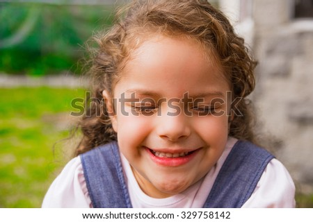 Young posing brunette girl closeup for camera, eyes closed and green background. - stock photo