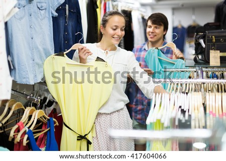 Young positive couple choosing clothes in the mall
