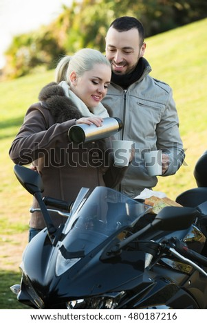 Young positive couple drinking coffee and chatting near motorcycle