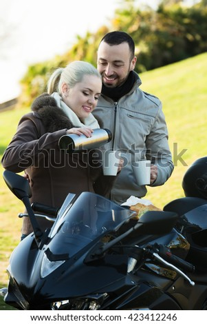 Young positive couple posing near motorcycle with sandwitches and coffee - stock photo
