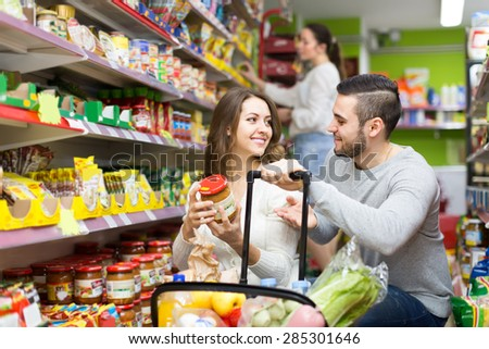Young positive family purchasing food for week at supermarket - stock photo