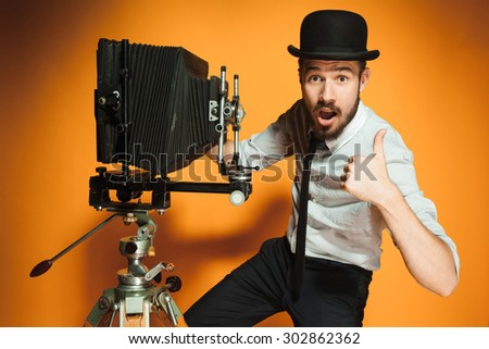 Young positive man in hat as photographer with retro camera on an orange background - stock photo