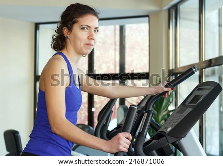 Young positive woman doing exercises with elliptical trainer in gym - stock photo