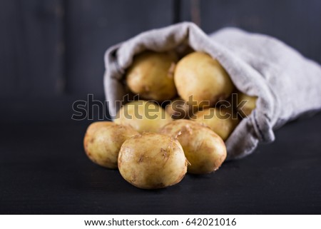 Young potatoes in a bag on a dark background.