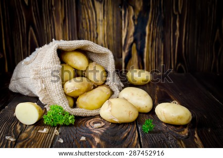 Young potatoes in a sack on a wooden table. Photo with copy space - stock photo