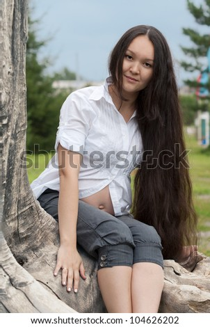 Young pregnant asian woman sitting in a park