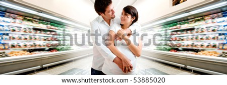 Young pregnant couple at supermarket - stock photo