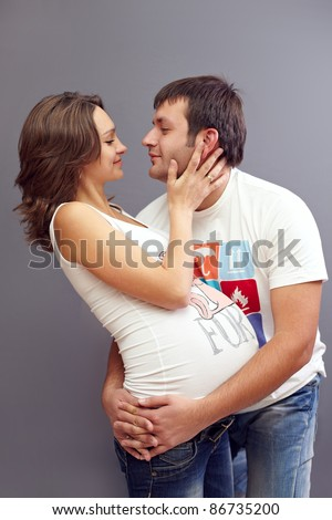 young pregnant couple in love. kiss - stock photo