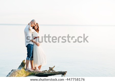 Young pregnant couple in love on summer sunny evening - stock photo