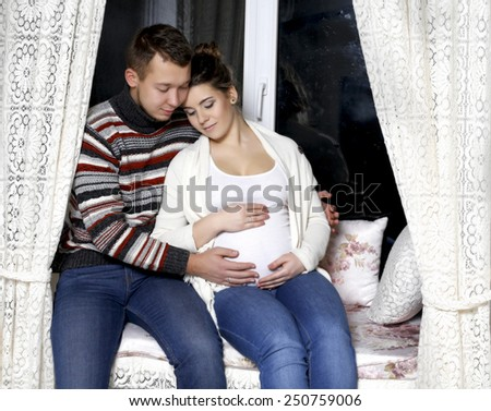 young pregnant couple is sitting on the windowsill, my husband put his arm around his wife and tummy - stock photo